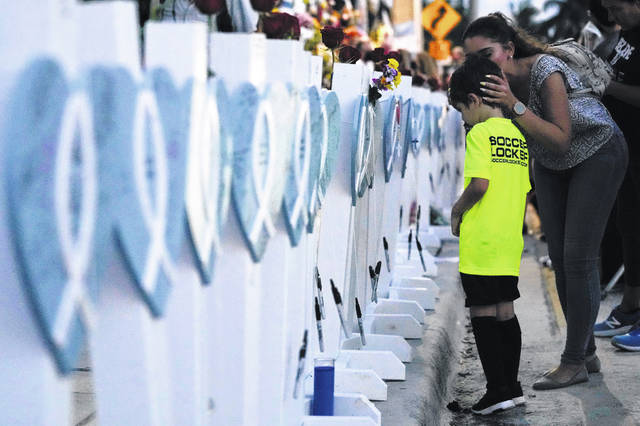 Claudia Benitez kisses the head of her son, David Barragan, 5, after he wrote a message on a wooden heart dedicated to Luis Bermudez, 26, one of the scores of victims of the Champlain Towers South condo building collapse, as people gathered for a multi-faith vigil near the site where the building once stood.