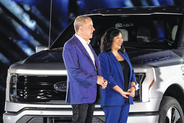 Bill Ford, who now goes by executive chair rather than chairman, stands next to Linda Zhang, chief engineer of F-150, after Ford Motor Co. unveils the electric F-150 Lightning at its World Headquarters in Dearborn, Michigan on May 19.