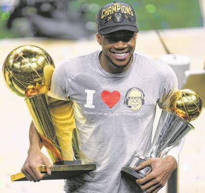 The Bucks' Giannis Antetokounmpo holds the NBA Championship trophy, left, and NBA Finals Most Valuable Player trophy following the series clinching victory Tuesday night against Phoenix in Milwaukee.