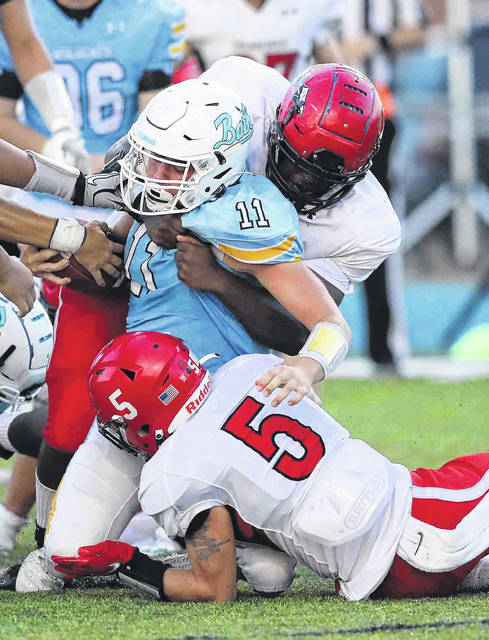 Shawnee's John Norris, top, and Chase Berry (5) tackle Bath's Ty Sibert during Friday night's game at Bath.