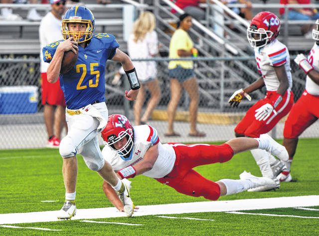 Nolan Schwinnen of Delphos St. John's gains yards against Lima Central Catholic's Carson Parker during Saturday night's game at Stadium Park in Delphos. See more high school football photos at LimaScores.com.