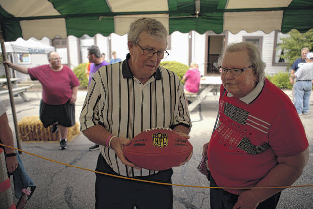 Fans take a look at an official NFL football, made only at the Wilson factory in Ada. Visitors to this year's football festival have a chance to win several gridiron themed prizes, including a special edition ball from last year's Super Bowl.