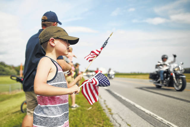 """Six-year-old Owen Dickman of Dublin waves a flag as he watches helicopters and motorcycles escort the military displays of the """"Eyes of Freedom"""" during the kick-off to a previous Fort Fest."""