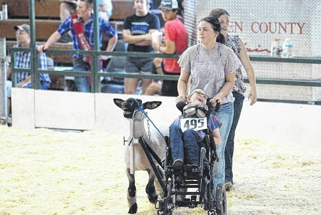 Jackson Lee smiles as his oldest cousin, Olivia Conley, pushes his wheelchair and he guides his lamb, Chester, around the showmanship arena at the Allen County Fair last Sunday.