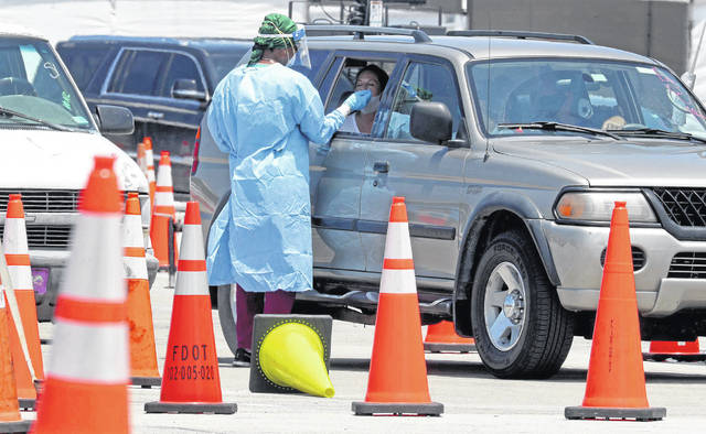 Health care workers administer free drive-thru COVID-19 tests at the Hard Rock Stadium in Miami Gardens, Florida, on July 15, 2020. (Mike Stocker/Sun Sentinel/TNS)