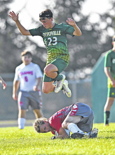 Ottoville's Andy Moorman leaps over Van Wert's goal keeper Mason Brinkman during Tuesday's match at Ottoville.