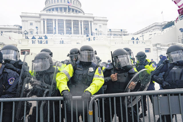 Police try to hold back protesters who gathered to storm the U.S. Capitol and halt a joint session of the 117th Congress on Jan. 6, 2021, in Washington, D.C.