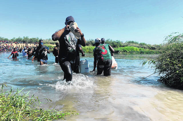 Migrants find an alternate place to cross between Mexico and the United States after access to a dam was closed Sunday in Ciudad Acuña, Mexico. U.S. officials said that within the next few days, they plan to ramp up expulsion flights for some of the thousands of Haitian migrants who have gathered in the Texas city from across the border in Mexico.