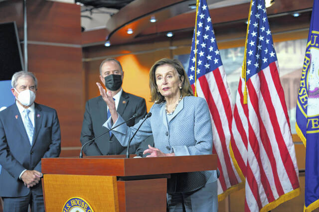Speaker of the House Nancy Pelosi, D-Calif., joined from left by House Budget Committee Chair John Yarmuth, D-Ky., and House Intelligence Committee Chairman Adam Schiff, D-Calif., talks to reporters Tuesday at the Capitol in Washington.