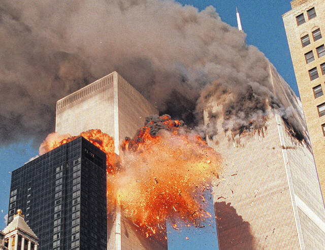 FILE - In this Sept. 11, 2001, file photo, smoke billows from one of the towers of the World Trade Center and flames as debris explodes from the second tower in New York. Relatives of the victims of the Sept. 11 attacks called Thursday, Sept. 2, for the Justice Department's inspector general to investigate the FBI's failure to produce certain pieces of evidence from its investigation. (AP Photo/Chao Soi Cheong, File)