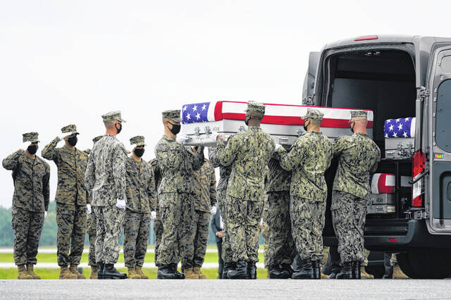 A carry team loads a transfer case with the remains of Navy Corpsman Maxton W. Soviak, 22, of Berlin Heights, into a transfer vehicle during a casualty return at Dover Air Force Base, Del., on Aug. 29 for the 13 service members killed in the suicide bombing in Kabul, Afghanistan, on Aug. 26.
