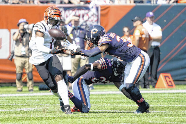 Cincinnati Bengals wide receiver Ja'Marr Chase, left, is unable to catch quarterback Joe Burrow's pass as Chicago Bears defensive back DeAndre Houston-Carson (36) and Kindle Vildor (22) defend during the first half of an NFL football game Sunday in Chicago.