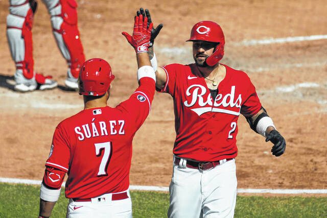 Cincinnati Reds' Nick Castellanos, right, celebrates his home run against the Washington Nationals with teammate Eugenio Suarez during the fifth inning of a baseball game Sunday in Cincinnati.