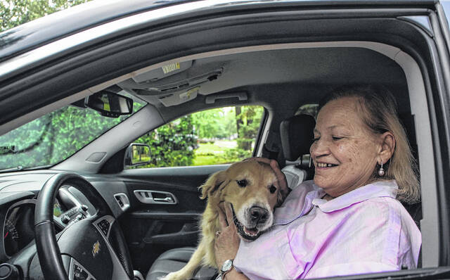 Margie Bauer of Harper Woods sits inside her 2015 Chevy Equinox with her dog Liberty on August 22, 2021. Bauer bought the vehicle because it would be dog-friendly and her two dogs could easily fit in the backseat.