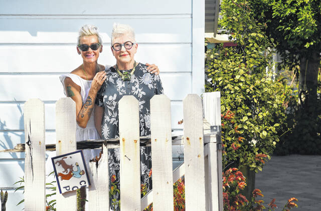 Maren McMillan hugs her mother, Patsy Spitta, in the backyard of Patsy's home in Altadena, Calif. Several laws have been passed allowing homes to be built in backyards.