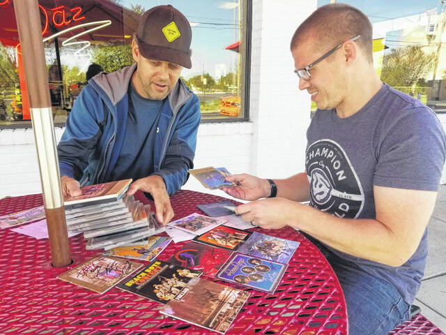 Beach Boy Al Jardine's assistant, Spud, presents fan Justin Evans with autographed CD covers in Lima on Sunday.