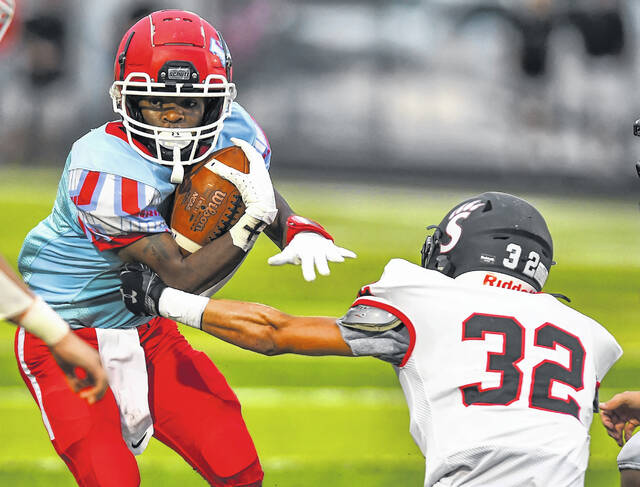 Spencerville's Cade Elling tries to get a hold of Lima Central Catholic's Quintel Peoples during Friday night's game at Spartan Stadium.