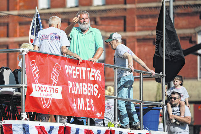 Union members wave to the crowd during the Labor Day parade in downtown Lima on Monday morning.