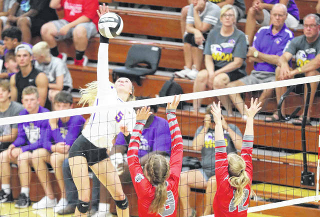 Leipsic's Peyton Heitmeyer hits a spike against Columbus Grove's Jaylen Sautter, left, and Sage Clement during Tuesday night's match at Leipsic. Head to LimaScores.com for more match photos.
