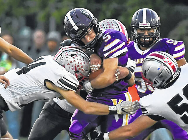 Leipsic's Caleb Ellerbrock fights for yardage against Columbus Grove's Landen Schroeder, left, during Friday night's game at Leipsic.