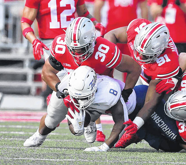 Tulsa's Deneric Prince gets stopped by Ohio State's Cody Simon (30) and Tyleik Williams during Saturday's game at Ohio Stadium in Columbus.