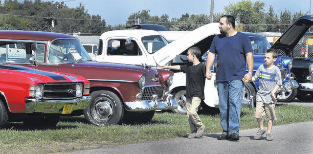 """William Maze of Lima walks with his two sons, JJ Maze, 8, and William Jr, 7, at the Rebel Run car show held in 2019 at the Allen County Fairgrounds. """"This is the first time for the boys,"""" Maze said."""