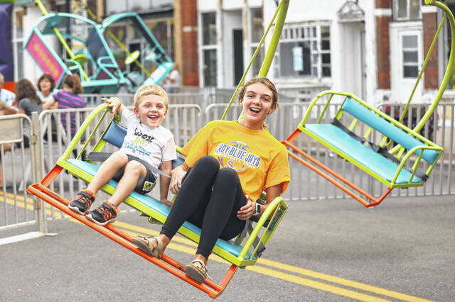 Seventh-grader Ellie Rahriig (right) and 3-year-old brother Levi, of Delphos, react to a ride during a past Canal Days in Delphos.