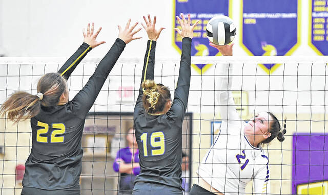 Leipsic's Kasey Brough hits a spike against Miller City's Lexi Banks, left, and Abi Teders during Tuesday night's match at Leipsic. See more volleyball photos at LimaScores.com.